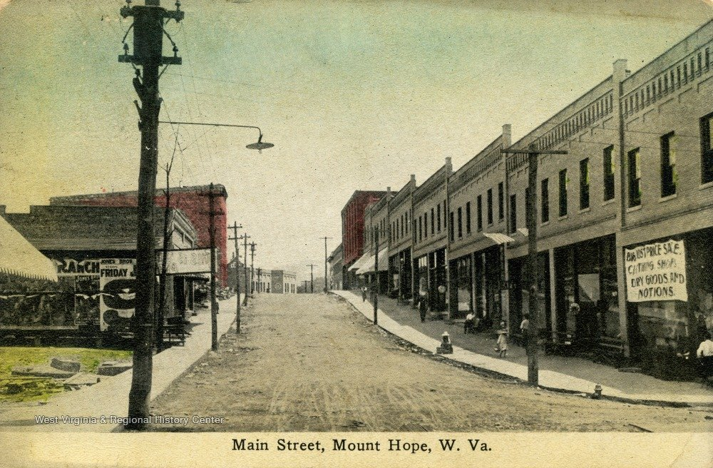 Postcard showing Garret and McNabb Block newly rebuilt.  Rubble from post fire can still be seen on the West side of Main St,