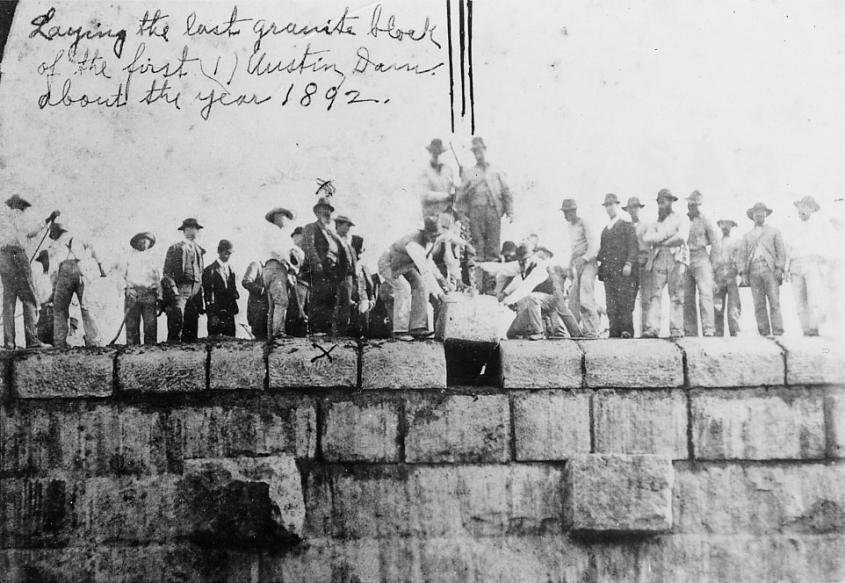 The final granite block being lowered into the Austin Dam, 1892. Photo from LCRA.