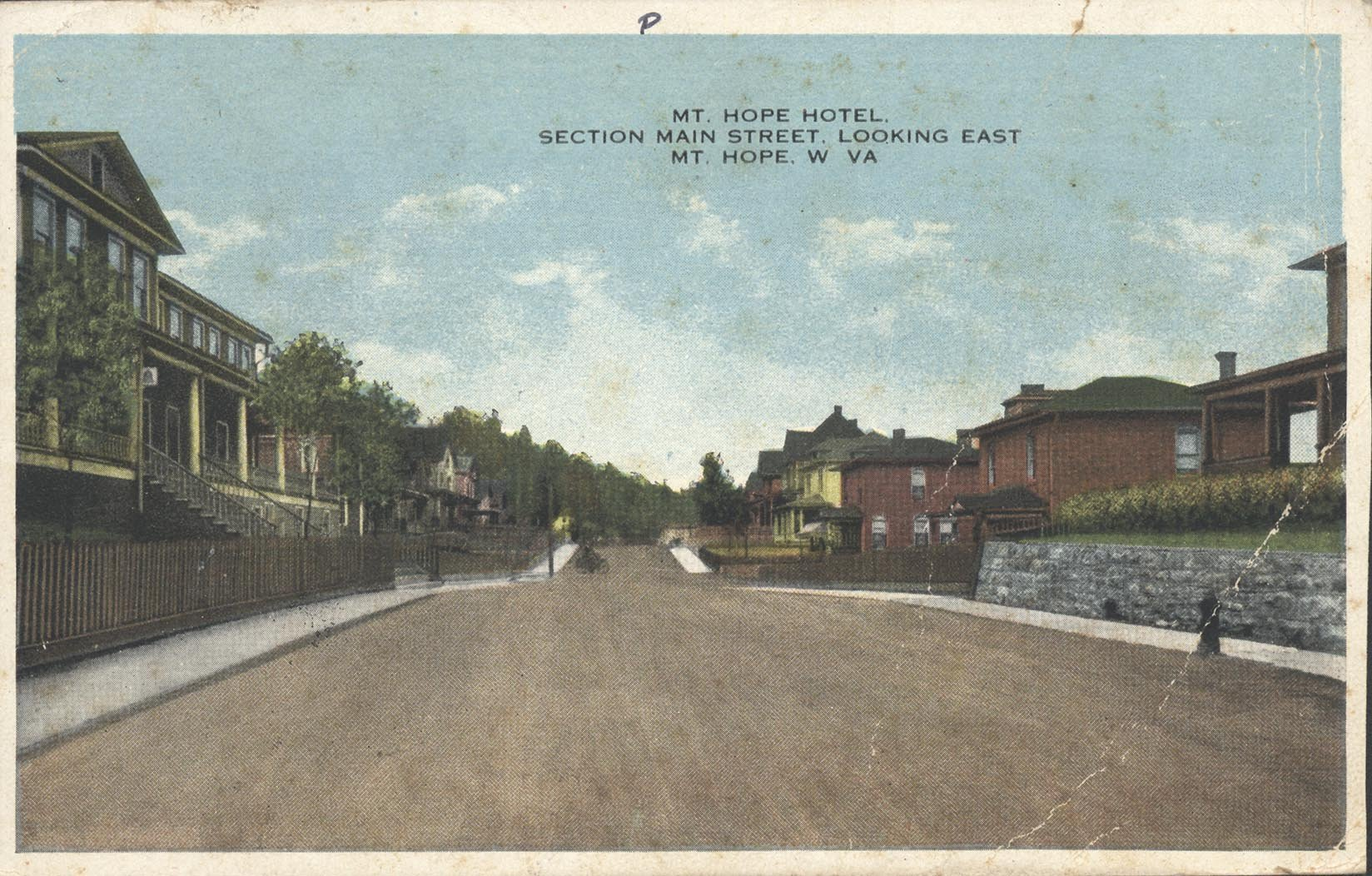 Post card of street view of the former Mount Hope Hotel (left) now known as the Mountainaire Hotel.  Notice how the porch is elevated away from Main St.  Picture provided by Marshall University, Rosanna Blake Library, Special Collections Department