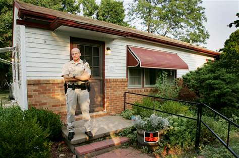 A police officer stands in front of Rader's house, located at 6220 Independence St. Park City, Kansas. The house was auctioned off to Michelle Borin at the price of $90,000 in 2005. It was later demolished by the city in 2007.