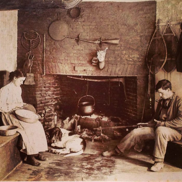 """Rowlie"" and Mary Robinson, with a canine friend, at work in front of the old kitchen's hearth in the early 1900s."