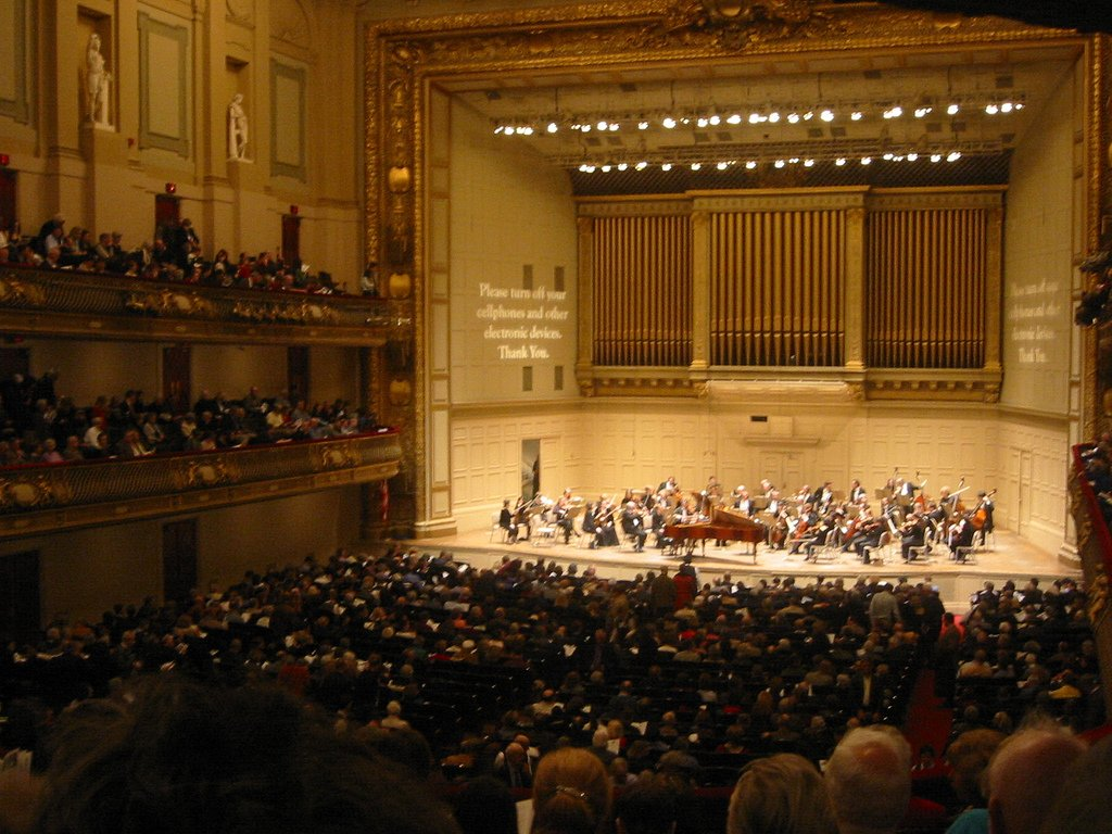 Interior view of Symphony Hall before a concert, 2006, courtesy of Wikimedia user mooogmonster. Notable features of the Hall visible from this angle are the organ, installed in 1949, and the ornate architecture which includes statues of mythological figur