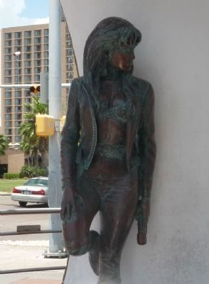 This is a statue of Selena. The statue is leaning against the wall, and it is on the right side of the monument.