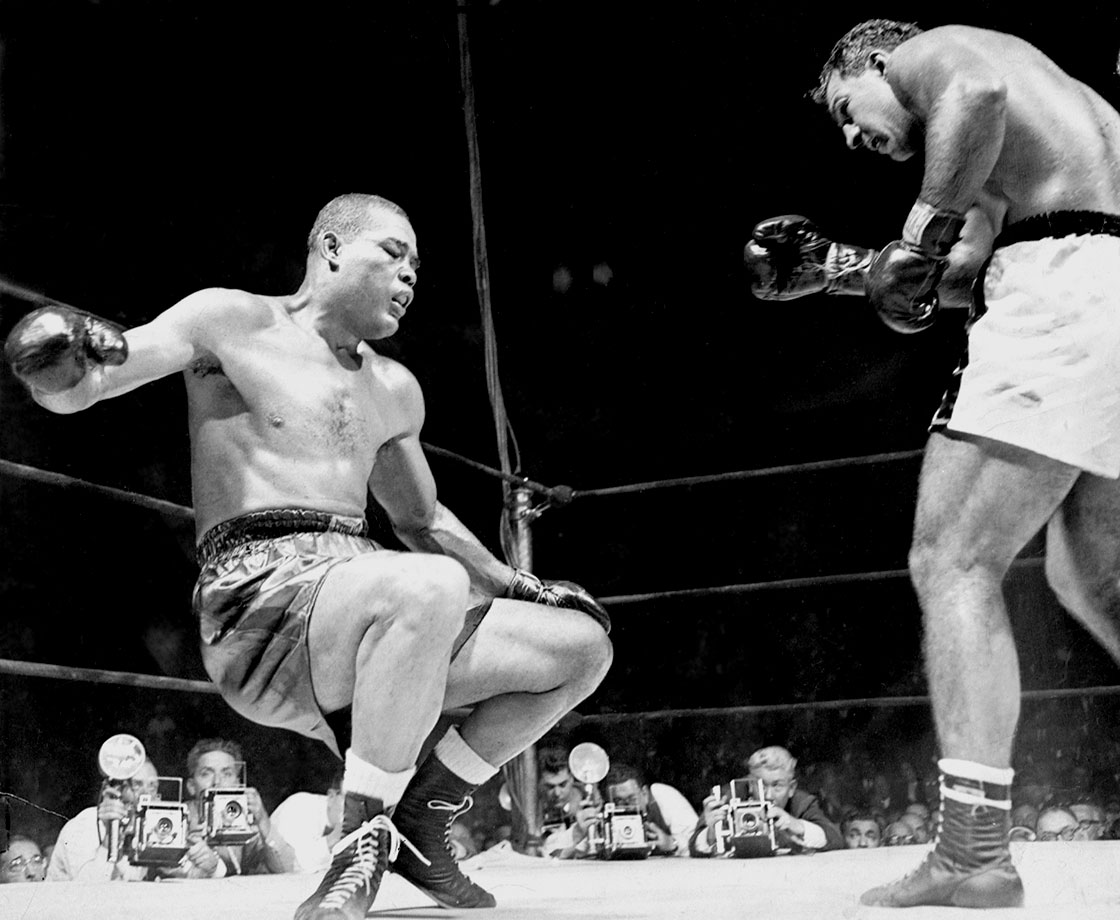 This photo was captured after Rocky Marciano knocked out Joe Louis in the 8th round of Louis' last fight. Marciano knocked him through the ropes in that final blow.