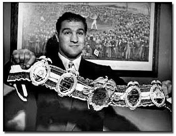 Rocky Marciano holding his heavyweight champion belt that he won in a historic fight against Joe Louis.