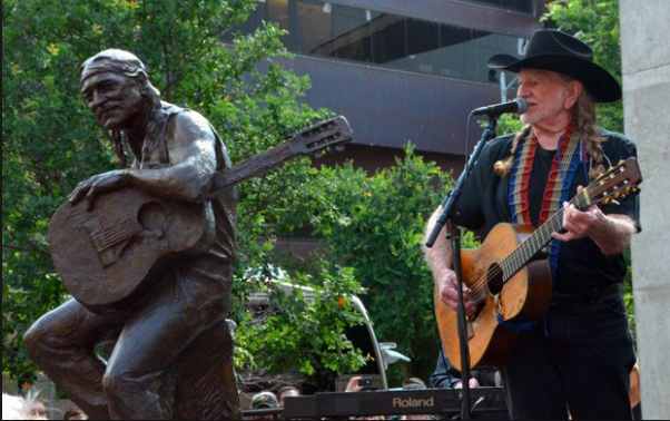 Willie Nelson performing beside of his statue in Austin, TX during the unveiling.