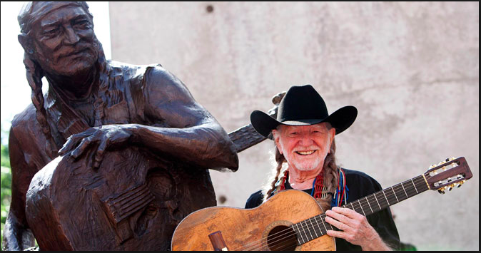 """Willie Nelson posing with his well known guitar """" Trigger"""" beside of his statue in Austin, Texas."""