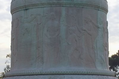 The base of the statue contains lightly sculpted images of Francis Scott Key, as well as other important figures from Greek mythology. This type of light sculpting into a horizontal medium is called a frieze in light relief. From The Historical Marke