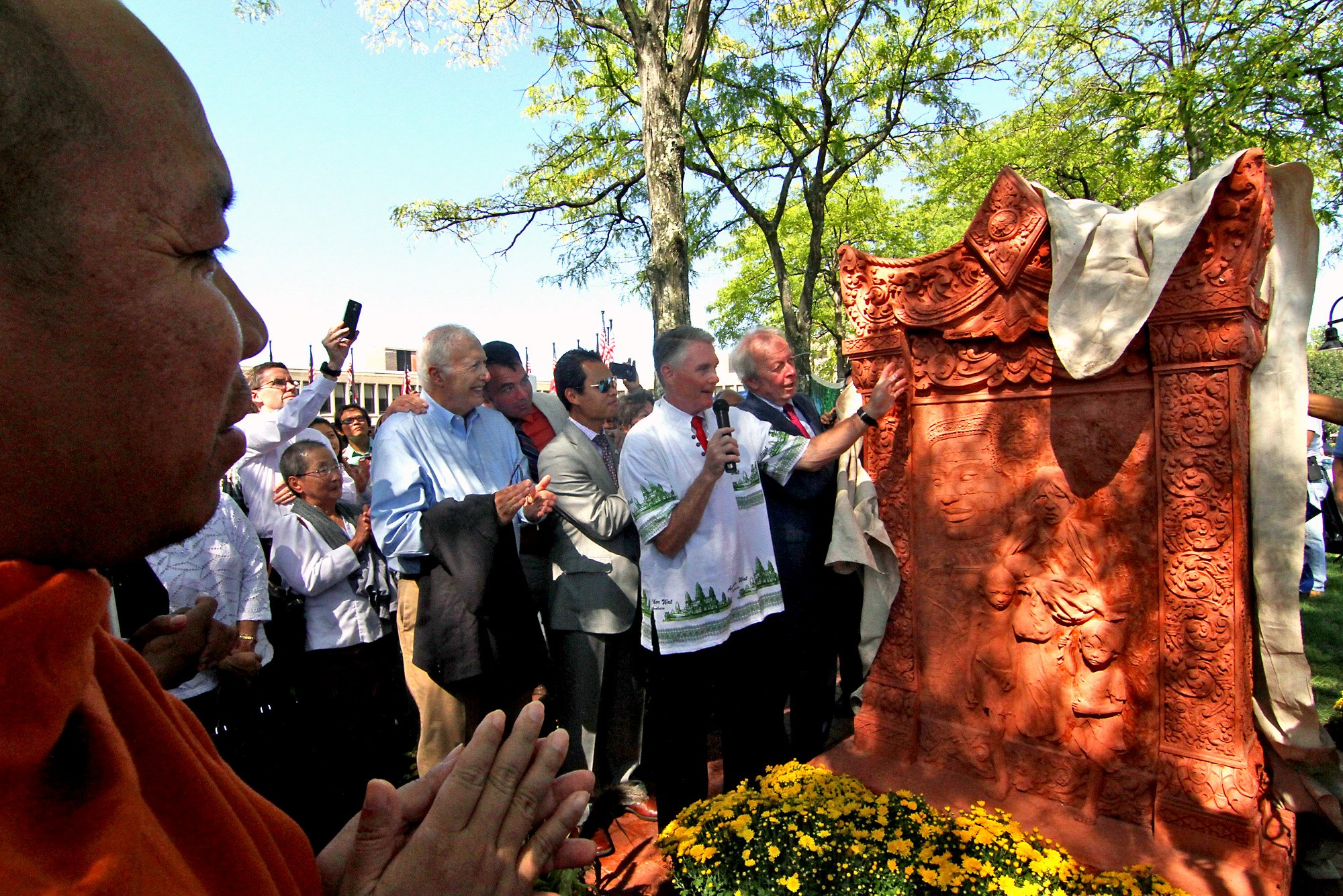 """A Buddhist Monk watches on left as Lowell City Councilor Rodney Elliott, along with other councilors and Mayor Ed Kennedy unveils the Khmer Monument in front of Lowell City Hall.""