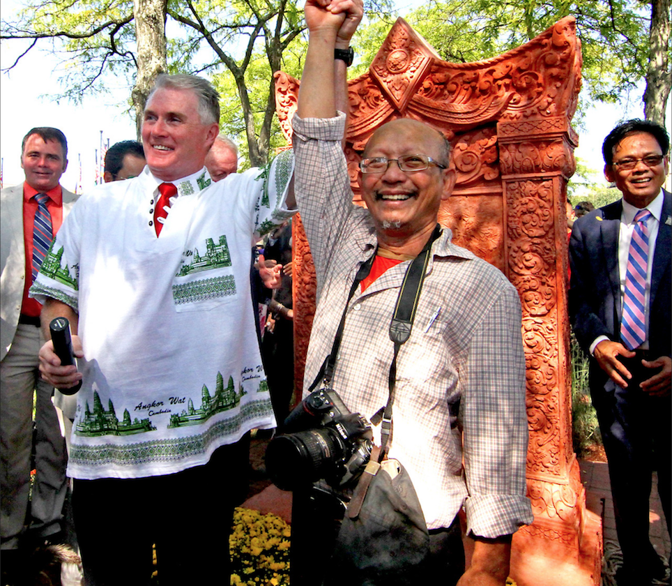 """Lowell City Councilor Rodney Elliott and Cambodian native and Lowell artist, Yary Livan raise arms in celebration after unveiling of the Khmer Monument that Livan designed.""