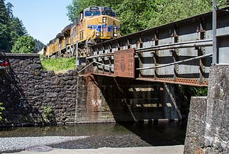 A diesel engine approaching Multnomah Falls bridge.