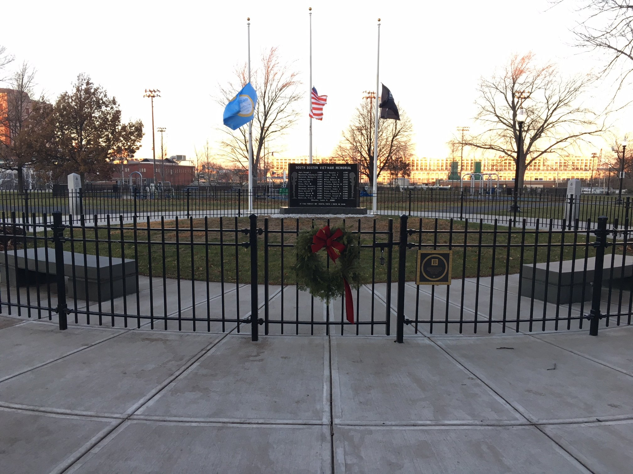 This wide-angle picture of the South Boston Vietnam Memorial shows the black memorial enclosed within a short gate and framed by the American, POW/MIA, and city of Boston flags.