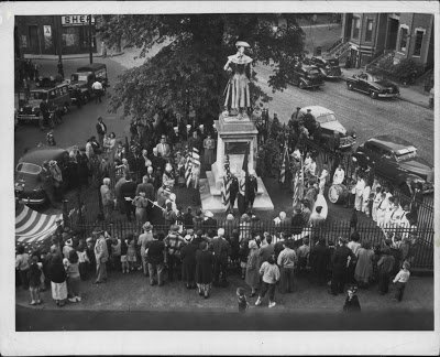 A photo circa 1940s. Exactly what is being celebrated is unknown, but it may be navy-related based on the two soldiers standing behind the statue. Note that a large tree had grown in front of the monument. It seems the ceremony adjusted for this.