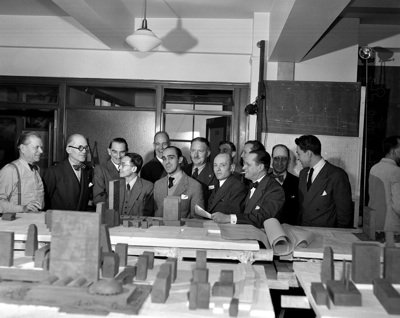 Le Corbusier (second from left) and Oscar Neimeyer (front and center) examine a model of their iconic design for the UN.