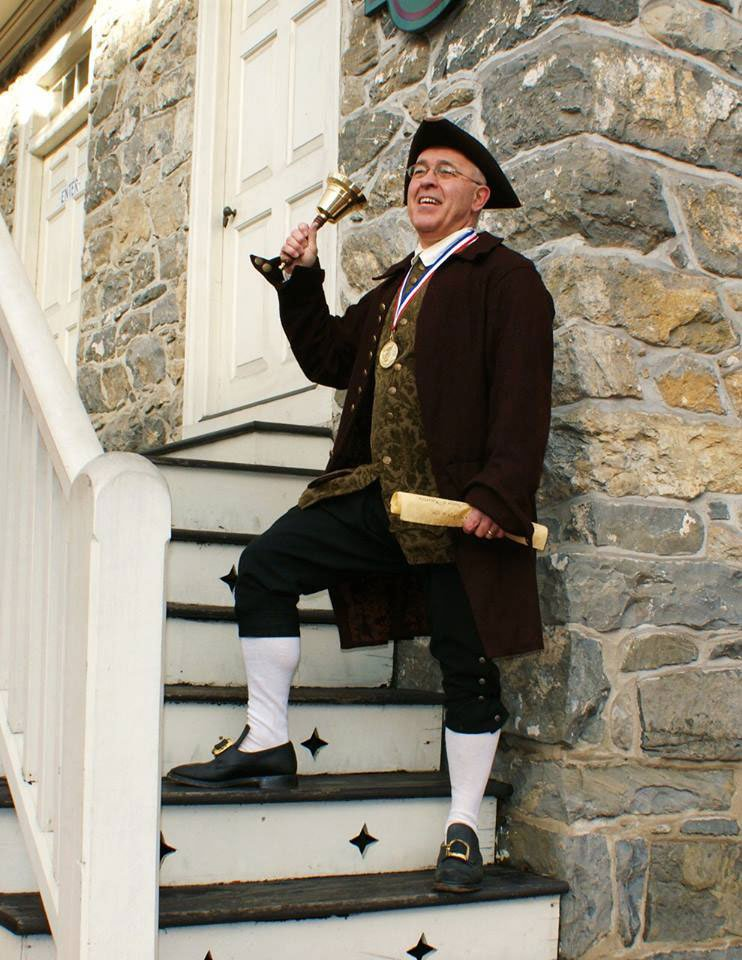 The Easton town crier on the steps of the Bachmann Publick House.