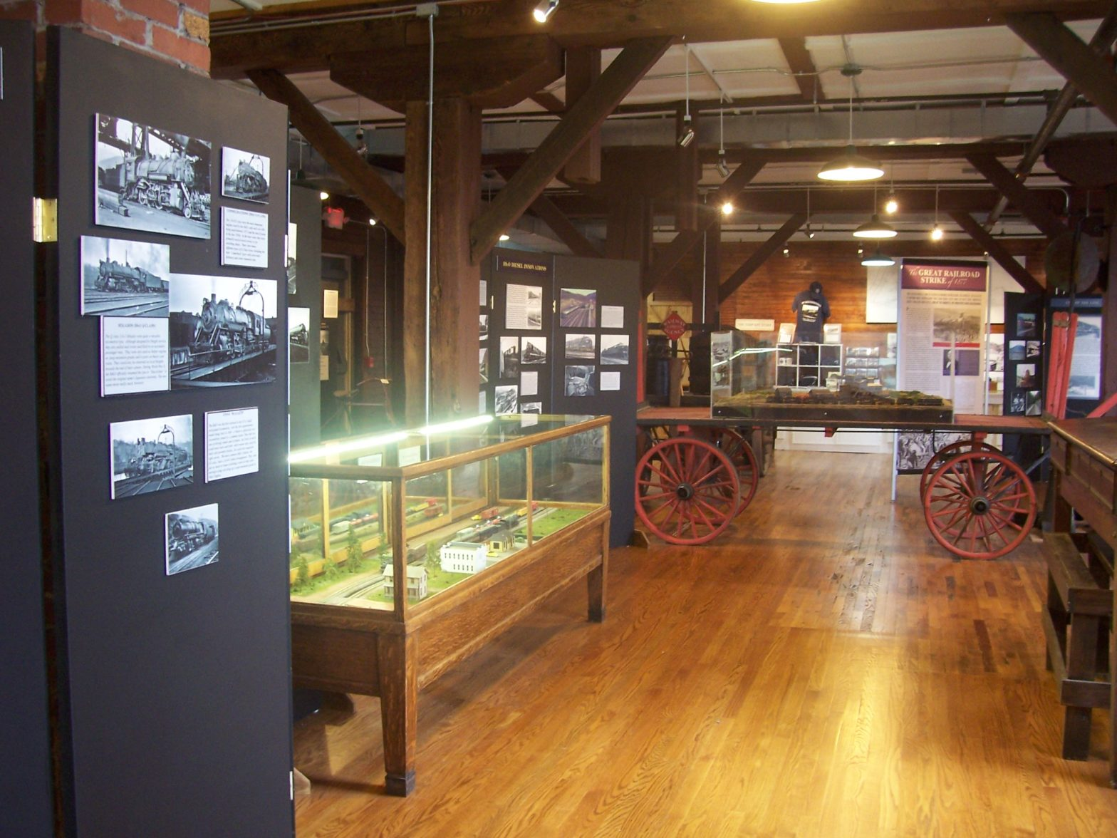 A view of museum exhibits with railroad machinery, cabinets with objects, and exposed Mill architecture.
