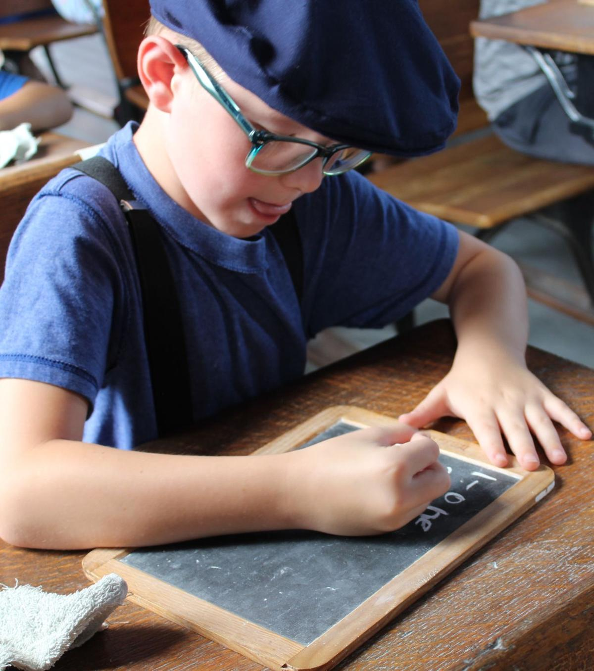Student writing on slate at their desk during schoolhouse lesson