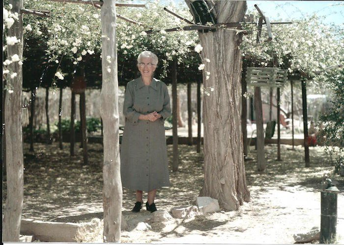 This is a photo of Ethel Macia with the rose tree.