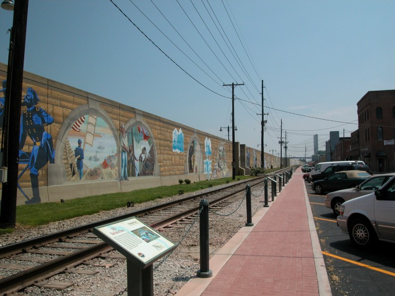 The floodwall features murals on both sides and many murals have interpretive signs explaining the person or event being depicted.