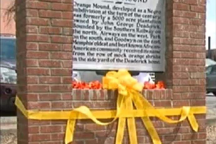 When vandals took the original historical marker, the community raised funds and created a new marker and a brick wall to protect it.