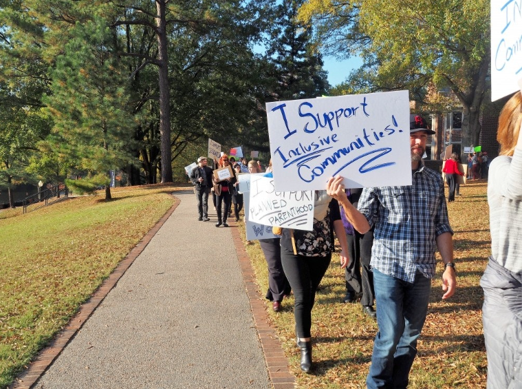 Professors and students gathering on the lawn outside of the library to protest injustices and fight for their beliefs: inclusivity of all communities.