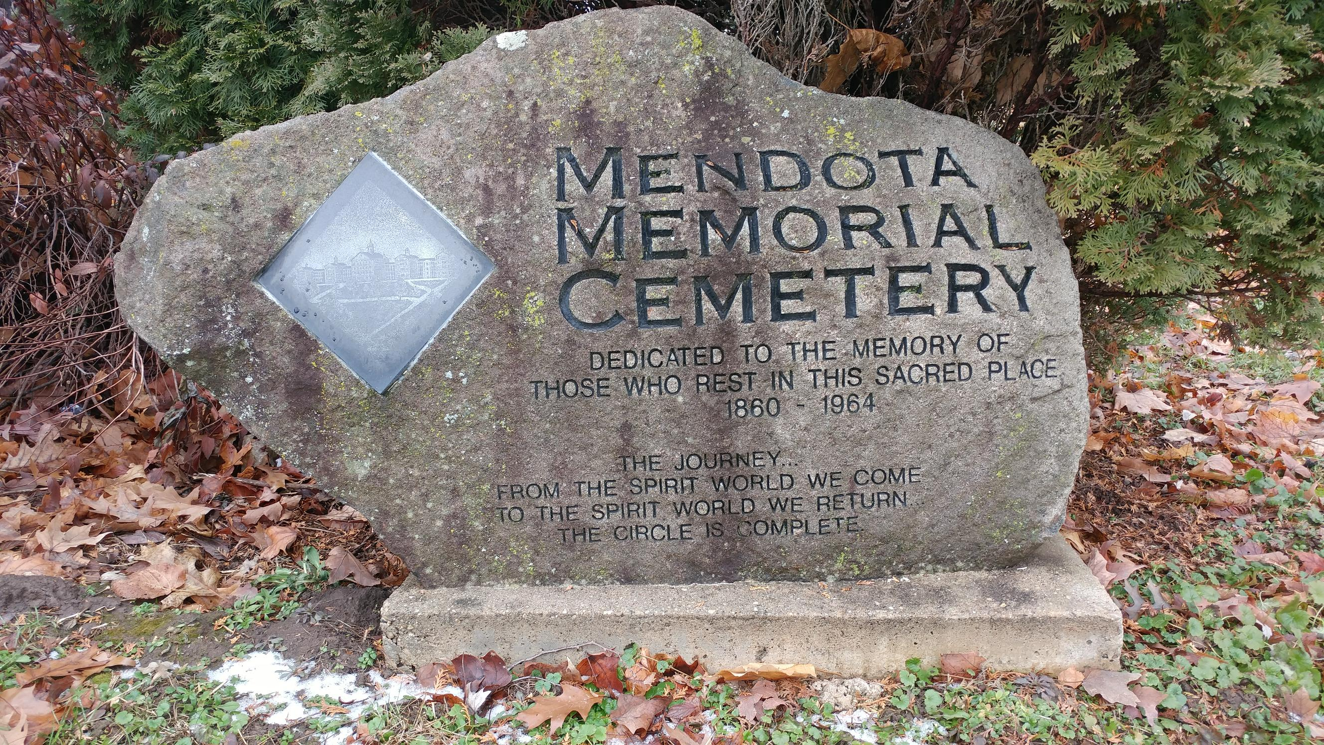 Close up of stone, which bears a picture of the original Mendota State Hospital and a poem.