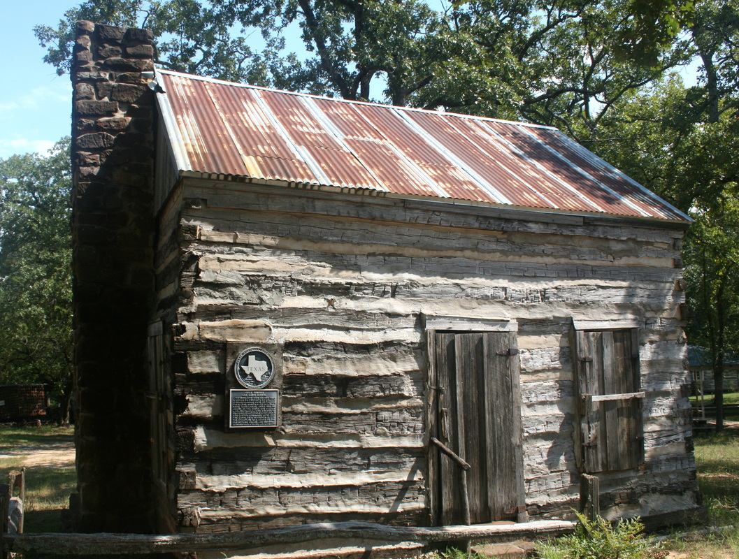 Photo of the Cold Springs Log Cabin/School at its resting place after being awarded as a Texas Historical Site in 1977