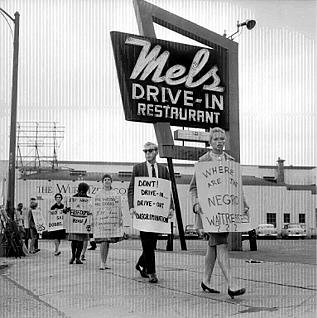 "Protesters carry signs asking ""Where are the Negro waitresses?"" and encouraging would-be patrons to ""drive out"" instead of ""drive in."""