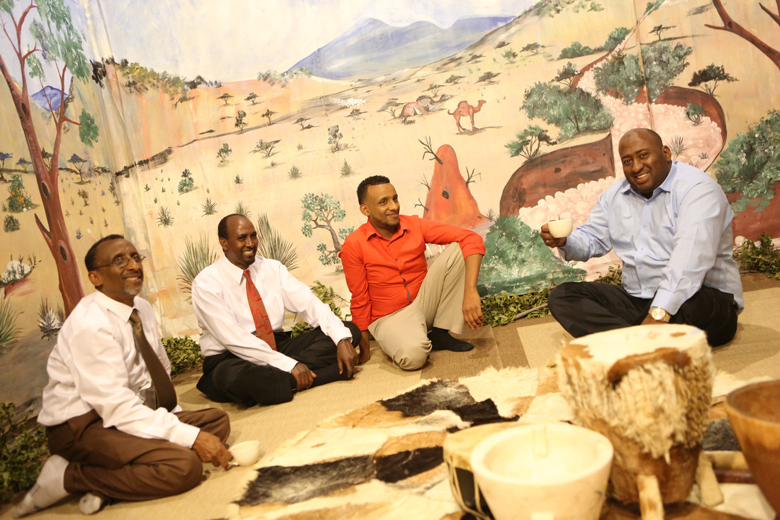 Osman Ali (Left) seated with visitors to the museum. Photo by Bob Stacke. Published with permission from The Somali Museum of Minnesota.