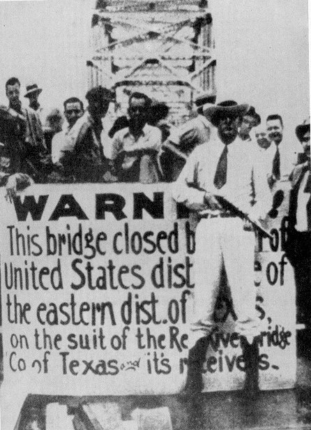 A Texas Ranger stands guard at the Denison-Durant free bridge with a sign which explains the reason for the bridge's closing. Reportedly, this image was featured in Time Magazine, showing that the controversy received popular attention.