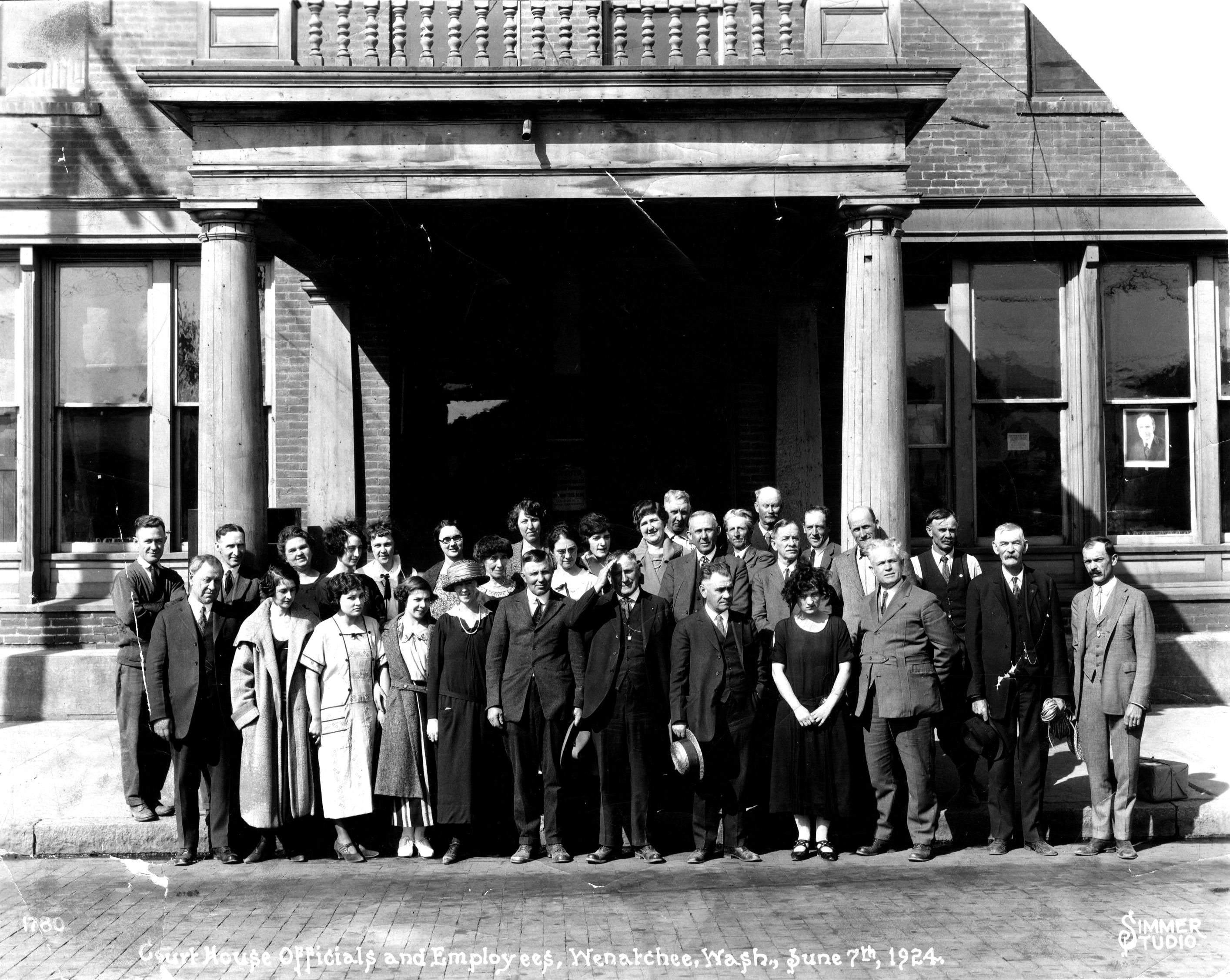 Chelan County officials and employees standing in front of the Chelan County Courthouse on Wenatchee Avenue, June 7th, 1924.  Moved to the new Chelan County Courthouse on June 9th, 1924.   Front row: L. D. Brown, State Examiner; Rachel McCroskey; Neva Martin (married name, Coppess); Helen Merriam (married name, Smith); Madge Cushing; E. C. Bowersox; J. H. (Jake) Miller; R. A. (Dick) Scheble; Fern Armstrong (married name, Collis); W. F. Buttles; Jack Dietch.   Second Row: Bill Luce; A. V. Shephard; Mrs. E. C. Bowersox; Grace McElhoe; Kathleen Beggs; Bessie Lewis (Mrs. E. G. Spencer); ?Chas. E. Buttles?; John Godfrey; Roy Larson; E. G. Spencer.   Third Row: Irene Trexler (married name, Jensen); Pearl Hall; Amy Johnson (married name, Stach); Mae Wanka; W. O. Tillman; unknown.   Four Row: Joe Parks; Howard Honner.