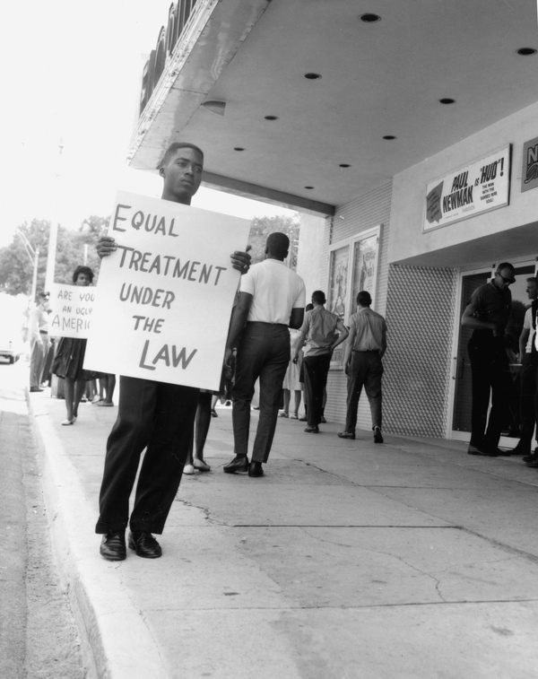 A man holds a sign outside of the theatre during the protest.