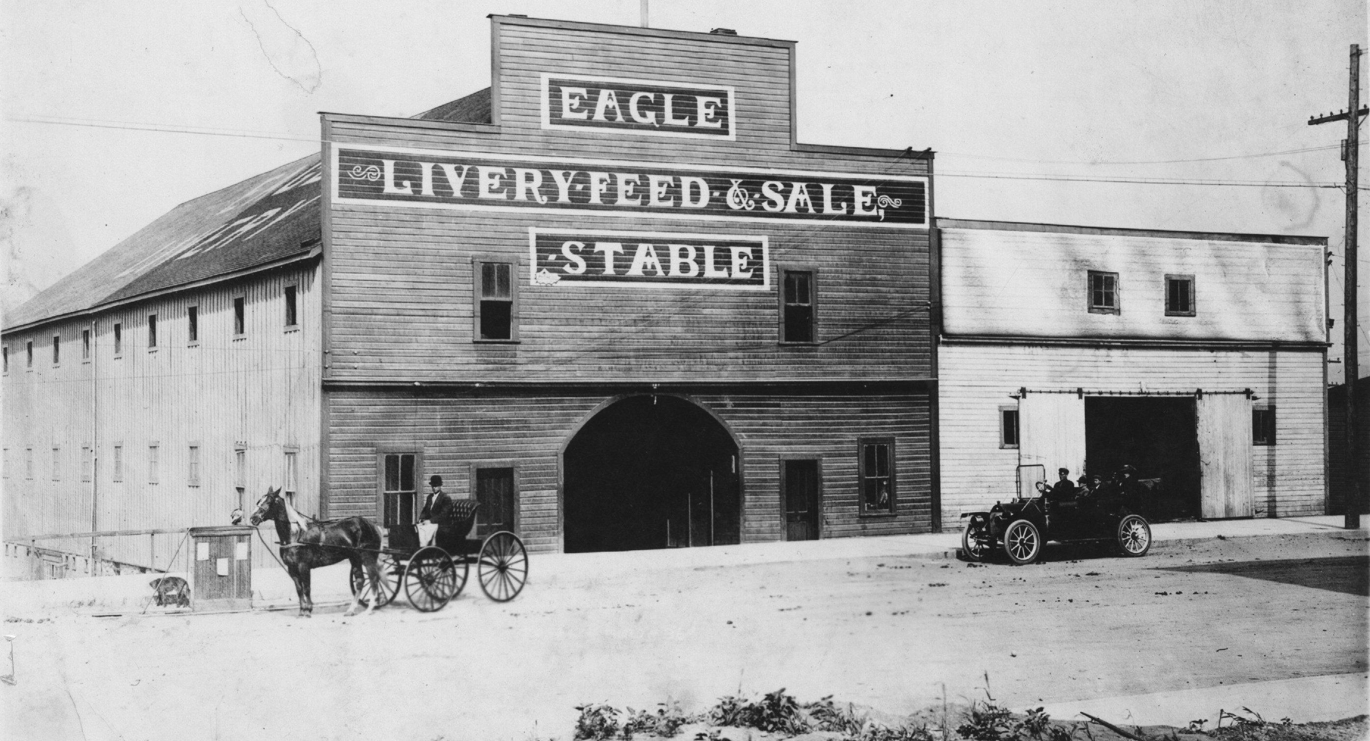 Eagle Livery Feed & Sale Stable building as it appeared before 1910.  It was founded in 1903.. Photo also shows someone in a horse drawn carriage and an automobile on the street in front.