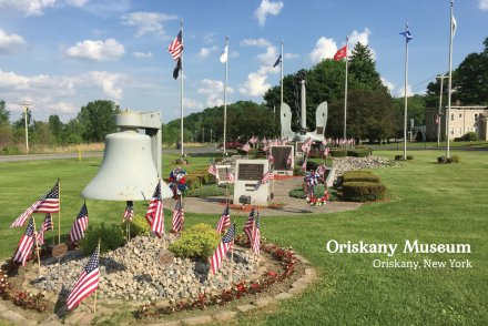 The starboard anchor and bell of the USS Oriskany serve as a memorial to its crewmembers.