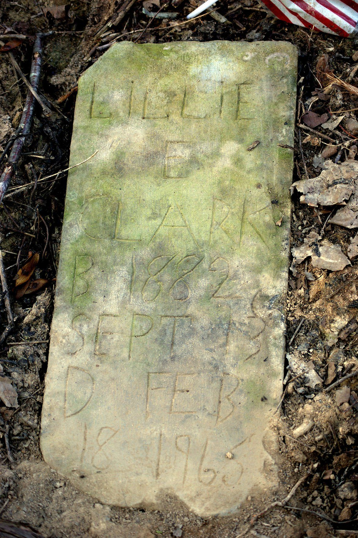 Hand-scratched headstone of Lillie E. Clark (1882-1965) found sunken in the earth during cleanup efforts in 2013