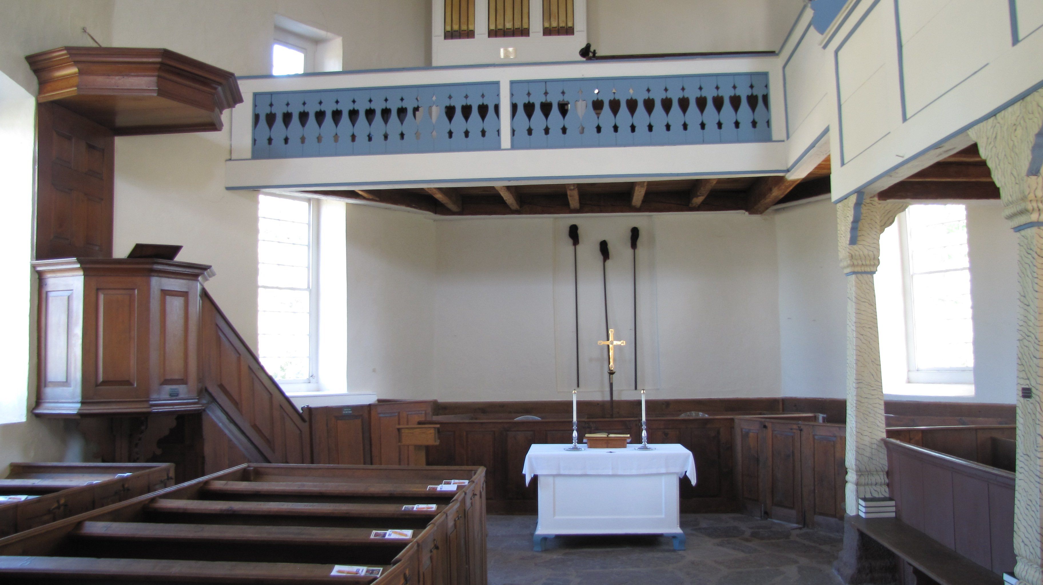 The church's interior, notice the red walnut pulpit on the left and organ loft which was added in 1752.