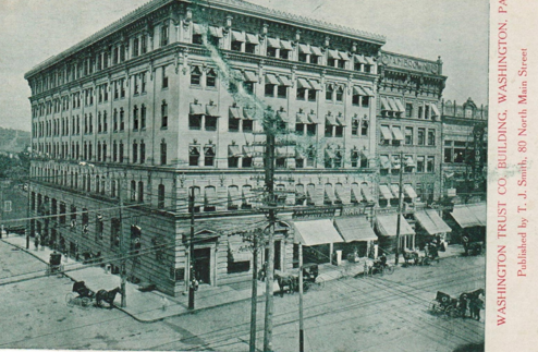 A postcard of the Washington Trust Building published sometime between 1903 and 1907 inferred by the grayscale illustration of the postcard itself and horse-drawn transportation depicted.