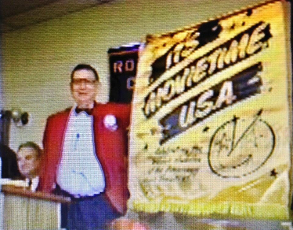 "Mr. W.P. Florence, Jr. in the 90's giving a presentation with his 1950s satin ""It's Movie Time USA"" banner about the history of theaters in Magnolia. This banner was used at the Cameo Theatre and is still owned by the Florence Heritage Foundation."