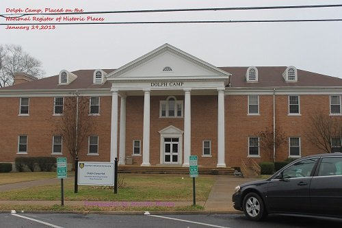 Dolph Camp is a two-story brick structure built in 1957 to house the school's music department. Its main entrance is sheltered by a single-story portico supported by six columns. The triangular pediment has an elliptical window. It was extensively