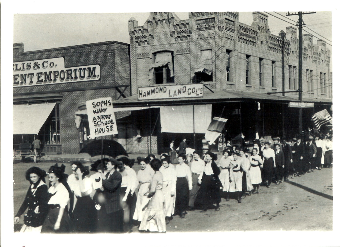 Boos Building in the background during a march for a new schoolhouse (no date).