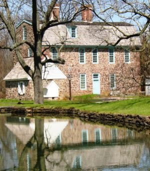 Keith House and the reconstructed summer kitchen as seen from across a small pond on site.