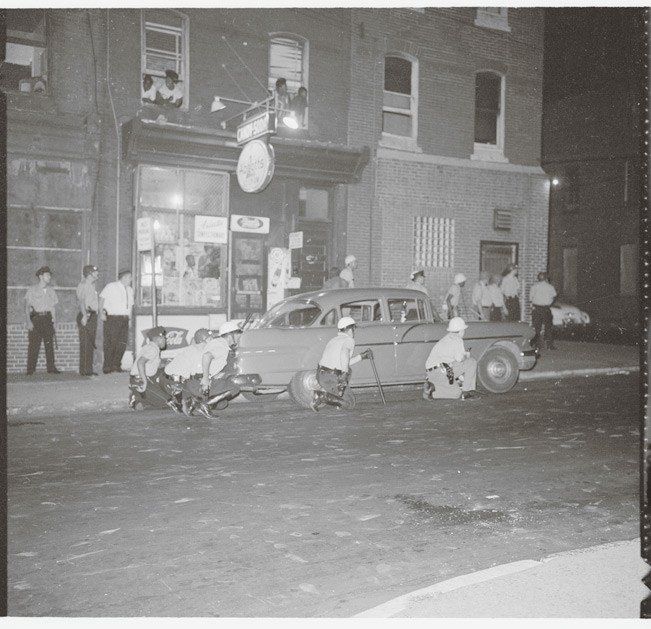 Police taking cover during the riots