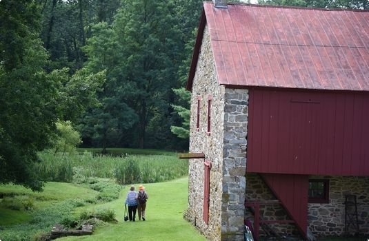 A couple walks past the 19th century barn.