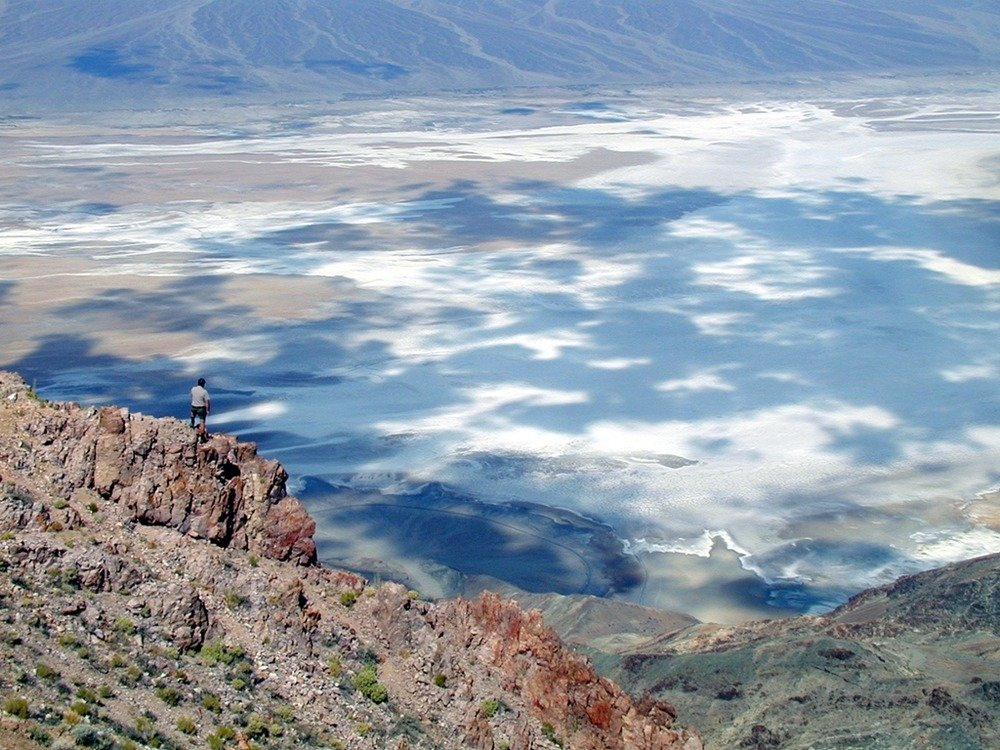 """A hiker looks over the valley on top of the Black Mountains. This spot is called """"Dante's View."""""""