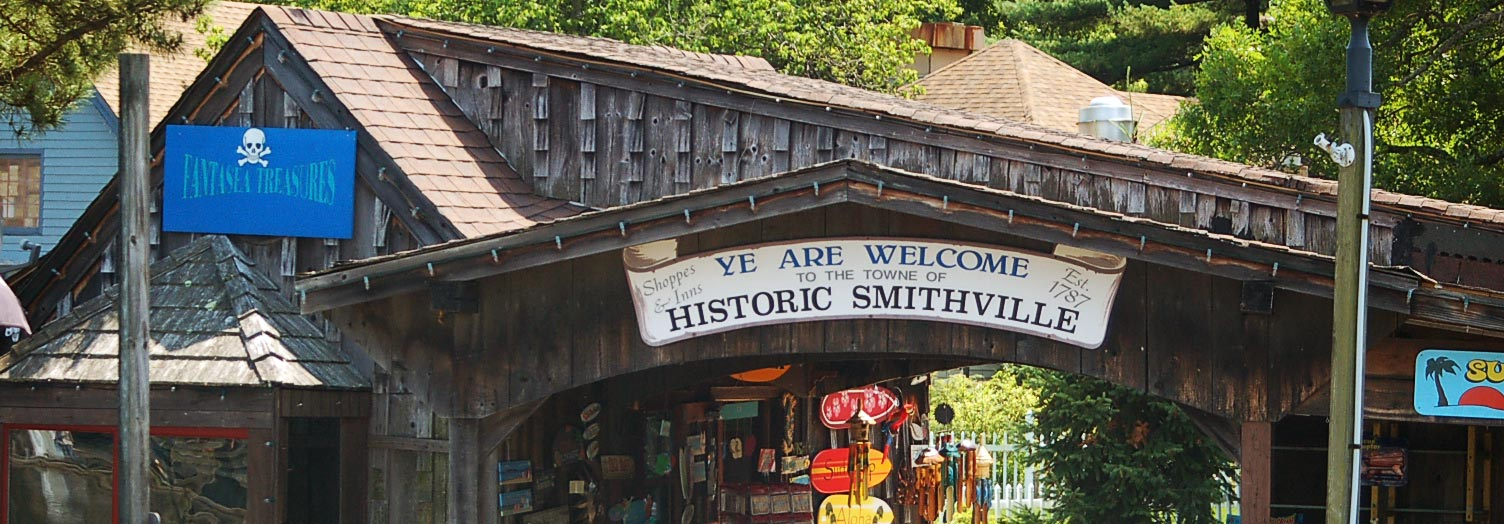 "This image shows the entrance/exit of the bridge to cross from one side of the town to the other where a picture worthy sign is posted labeled ""Ye are Welcome to the Towne of Historic Smithville."" Photo from historicsmithville.com."