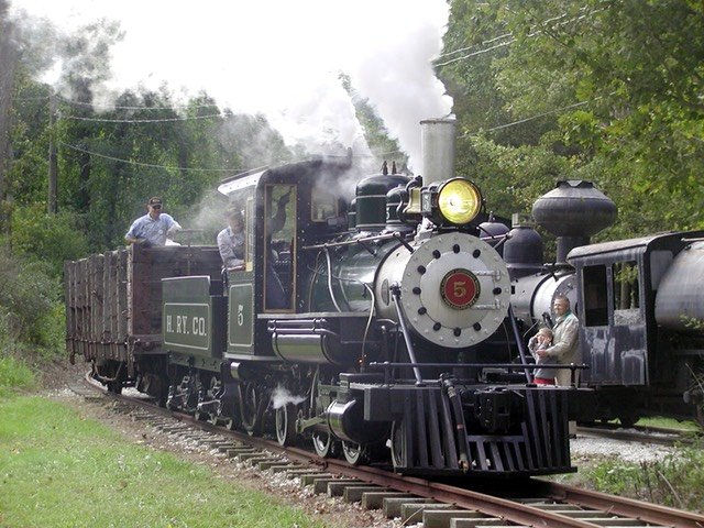 Steam and diesel locomotives run on a narrow gauge track.