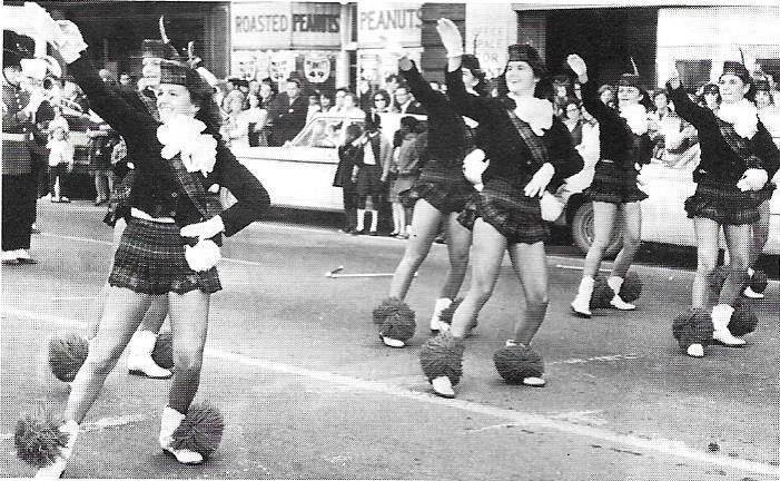 HEHS cheerleaders march by The Peanut Shoppe in 1967