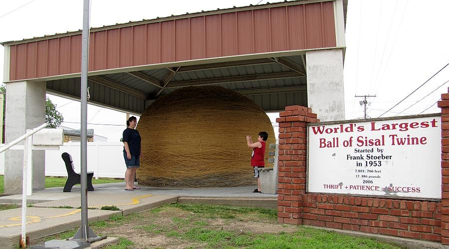 Another picture of the World's Largest Ball of Twine in the shelter that the Cawker City built and paid for and tourist taking pictures with it.