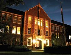 The front of the High School Building at night.