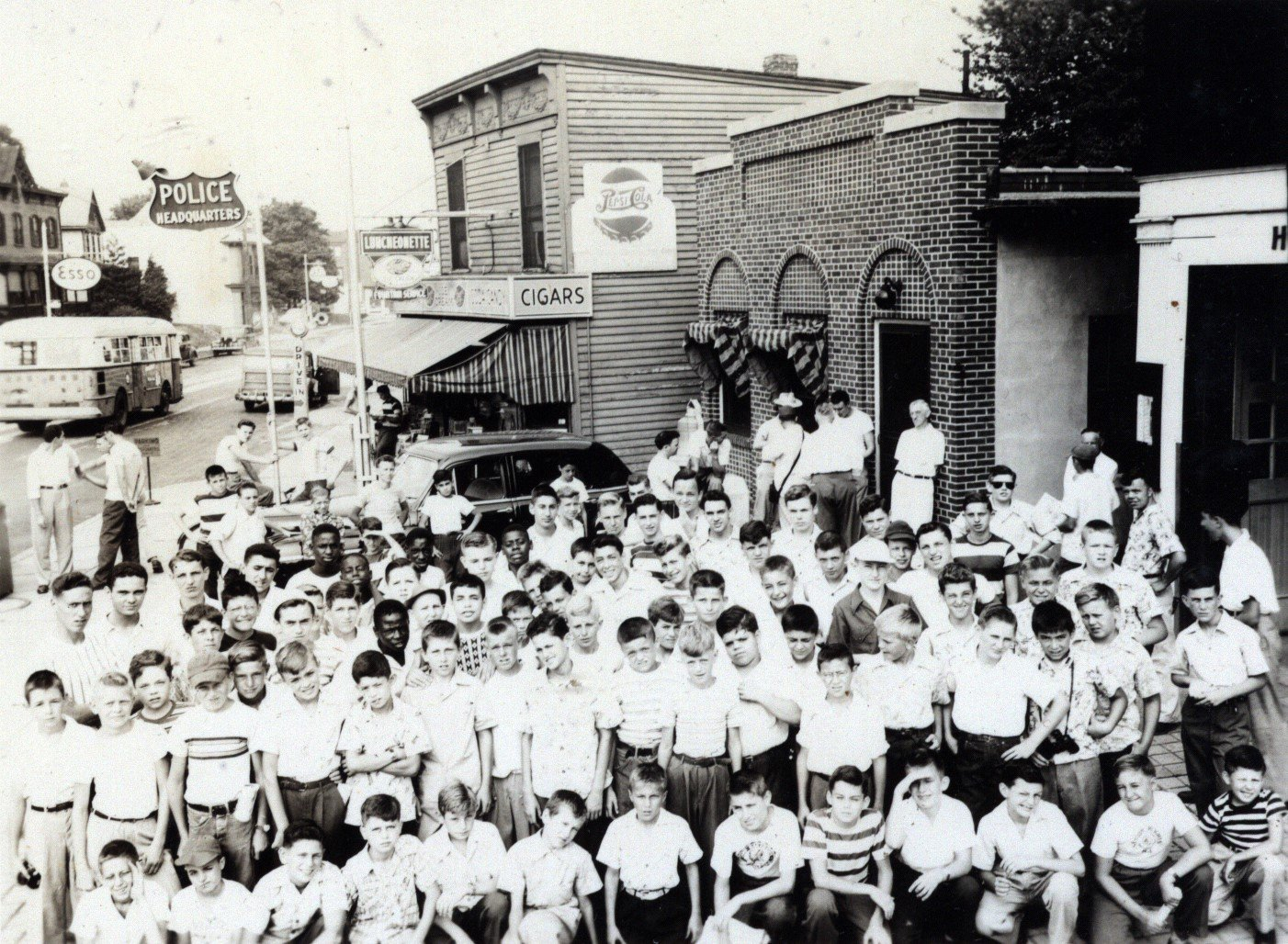 This is a photo from 1949 showing a group of children wait to be picked up for a Yankee's game for a sponsored night out by the Highland Park Police Department, which was located in the 1-story brick building in the center. In 2018-19, this Alexander Merc